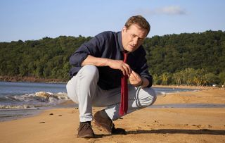 Star Ardal crouches on a beach in the new series of Death in Paradise