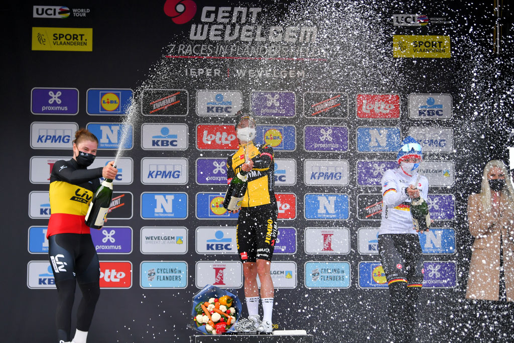 WEVELGEM BELGIUM MARCH 28 Podium Lotte Kopecky of Belgium and Team Liv Racing Marianne Vos of Netherlands and Team Jumbo Visma Lisa Brennauer of Germany and Ceratizit WNT Pro Cycling Team Celebration during the 10th GentWevelgem In Flanders Fields 2021 Womens Elite a 1417km race from Ypres to Wevelgem Mask Champagne Covid Safety Measures GWE21 GWEWomen FlandersClassic UCIWWT on March 28 2021 in Wevelgem Belgium Photo by Luc ClaessenGetty Images