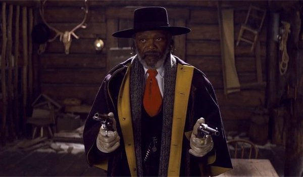 The Hateful Eight Samuel L. Jackson stands with two guns drawn at the camera