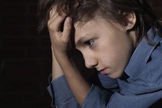 A sad kid sits alone.