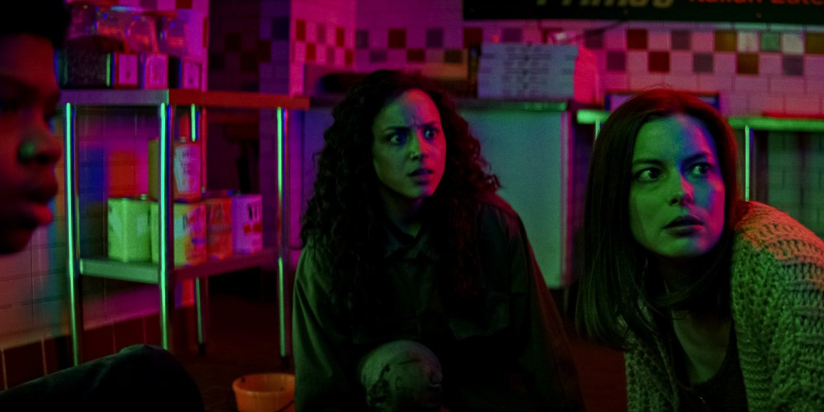 Benjamin Flores Jr., Kiana Madeira, and Gillian Jacobs looking horrified at the mall in Fear Street: Part 3 - 1666.