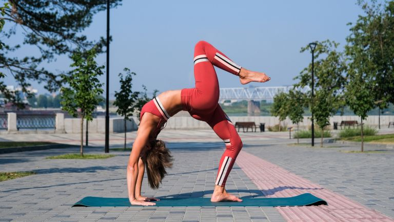 Woman does the Bridge or Upward Bow yoga pose