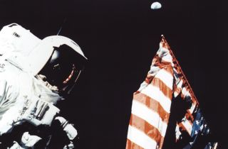 Astronaut Harrison Schmitt with the American flag and the Earth in the background, during a trek on the lunar surface as part of the Apollo 17 mission.