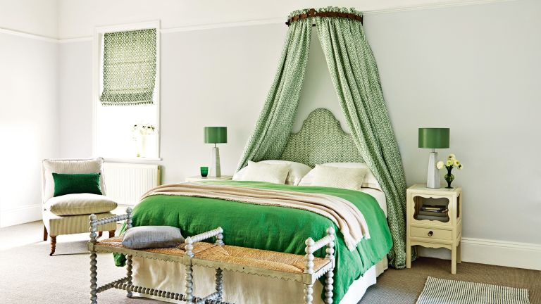 An example of green bedroom ideas showing a bed with a green velvet throw and matching upholstered headboard and canopy, with a green and white patterned fabric