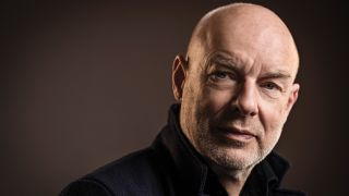 Brian Eno 2016 solo shot against a dark background