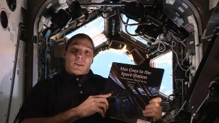 """NASA astronaut Mike Hopkins holds the book """"Max Goes to the Space Station"""" inside the real-life space station's Cupola observation deck. The book, written by author Jeffrey Bennett, is part of Story Time From Space."""