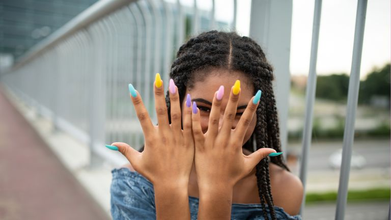 Teen showcasing multicolored long nails, fashion lifestyle concept.