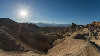 The dramatic badlands of Zabriskie Point in Death Valley lit by the late afternoon sun.