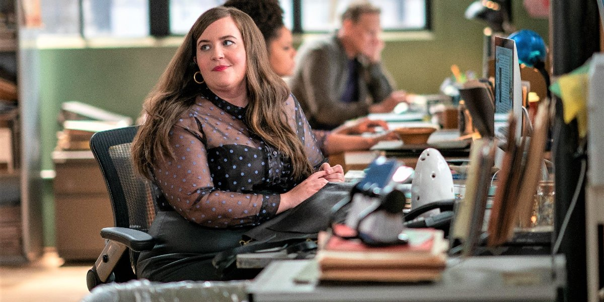 Aidy Bryant looks over her shoulder at her desk in Shrill.
