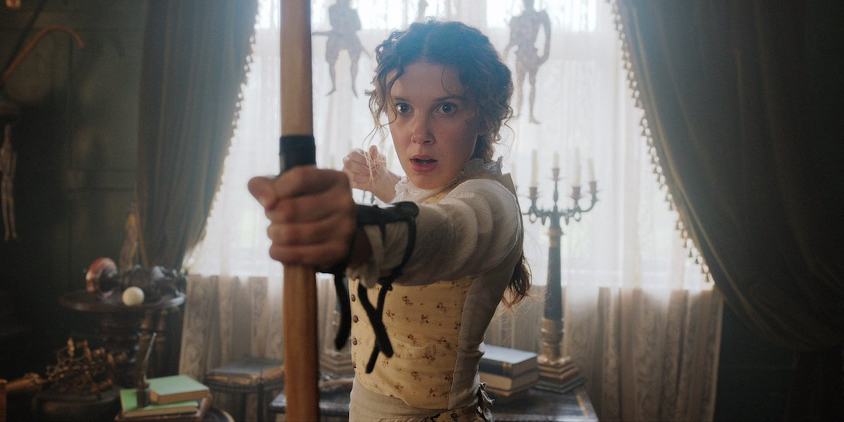 Enola Holmes (Millie Bobby Brown) pulls back the strong of an arrow.