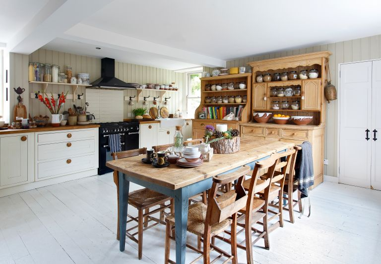 kitchen with wooden table, pantry and white cabinetry