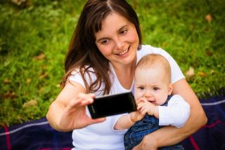 A mom holds her baby and snaps a selfie.
