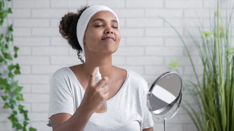 Young woman with eyes closed spraying facial mist at home - stock photo