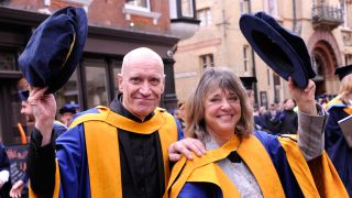 A picture of Wilko Johnson and Suzi Quatro with their honorary doctorates at Anglia Ruskin University