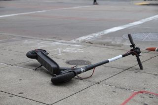 An electric scooter lying on the street.