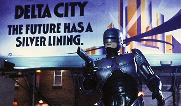Robocop takes aim in front of a billboard