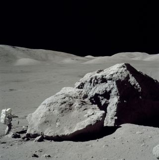 Astronaut Harrison Schmitt standing next to boulder during third EVA of Apollo 17, NASA's final manned mission to the moon.