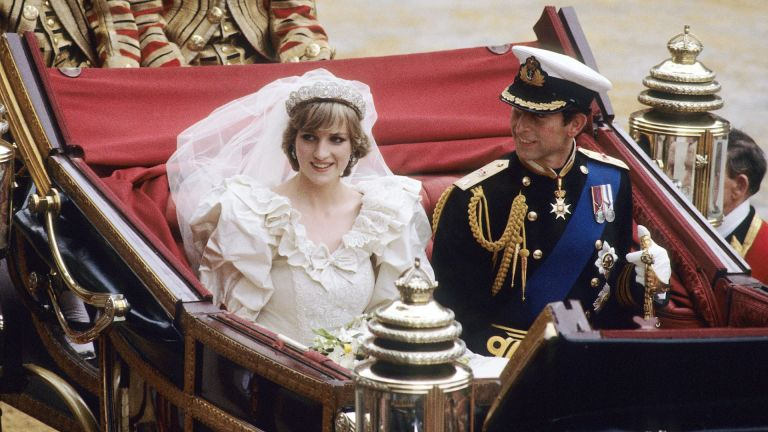 Princess Diana and Prince Charles ride in an open carriage on their wedding day