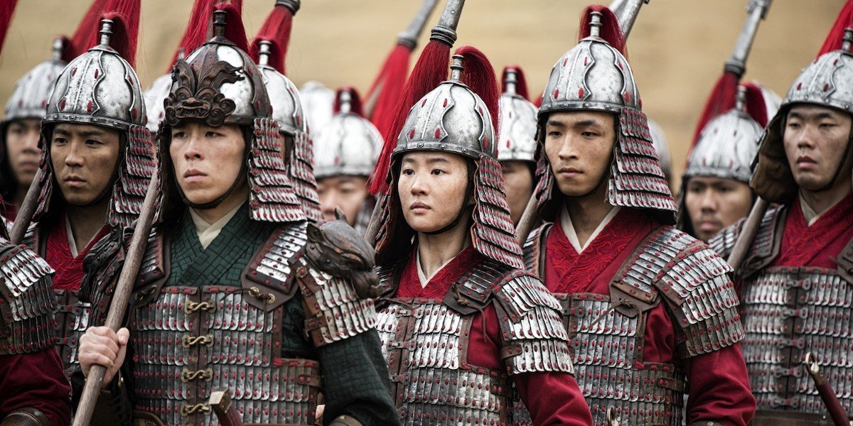 Mulan stands among her fellow soldiers, armed and ready for battle.