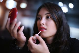 A woman applies lipstick with a small mirror.