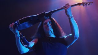 Close-up of Testament guitarist Alex Skolnick on stage, holding his guitar aloft