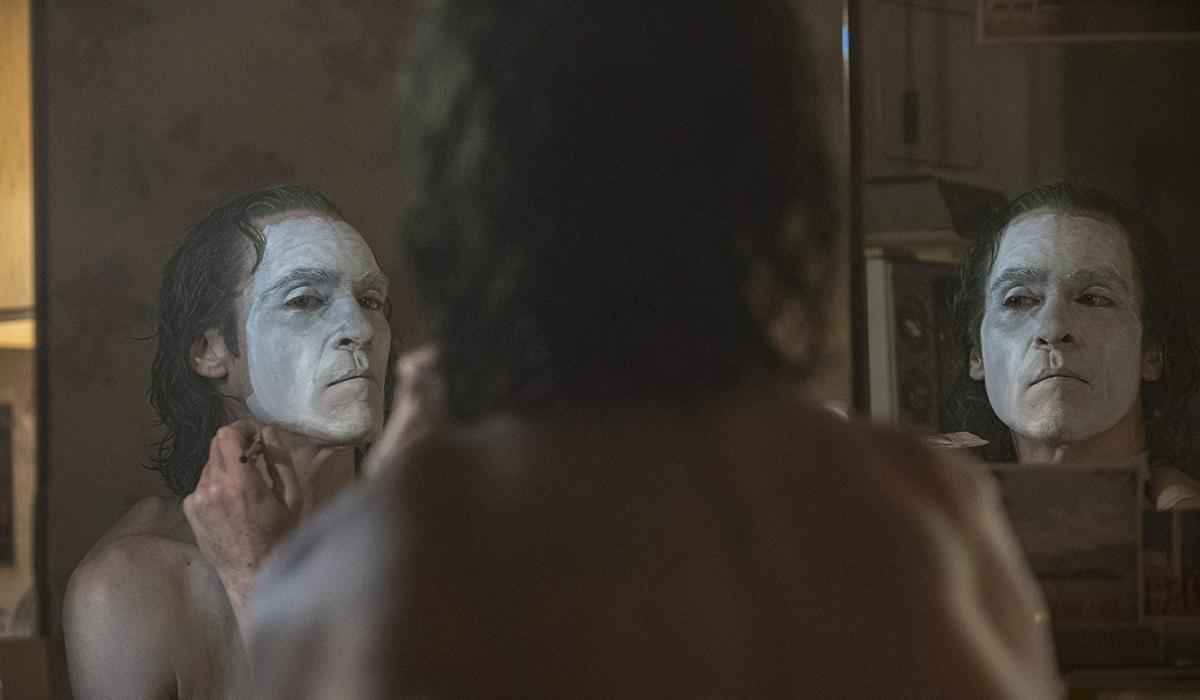 Joker Arthur paints his face as a transformation