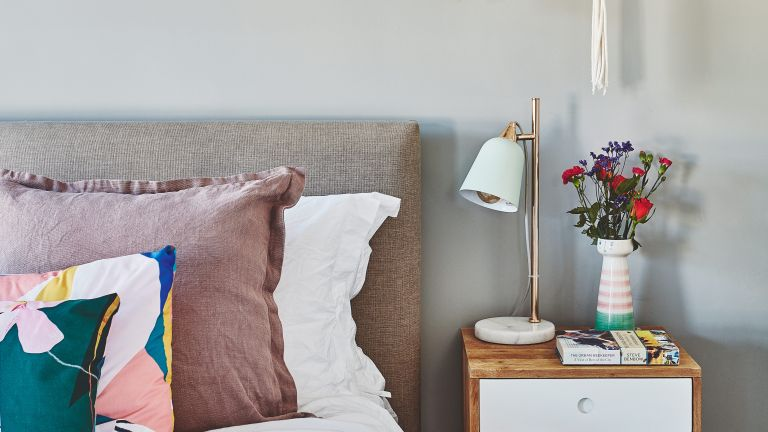Grey bedroom with pink cushions