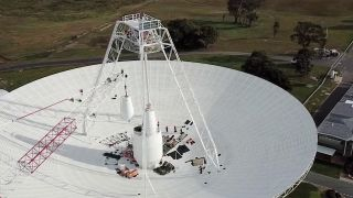 Crews conduct critical upgrades and repairs to the 230-foot-wide (70 meters) Deep Space Station 43 radio antenna in Canberra, Australia. In this image, one of the antenna's white feed cones, which house portions of the antenna receivers, is being moved by a crane.