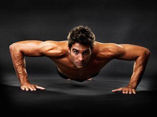 Full length of muscular guy doing pushups on black background