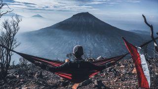 best hammocks: a camper sat in a hammock admiring a mountain