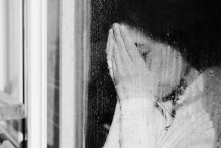 A woman looks out a window during a dreary winter day.