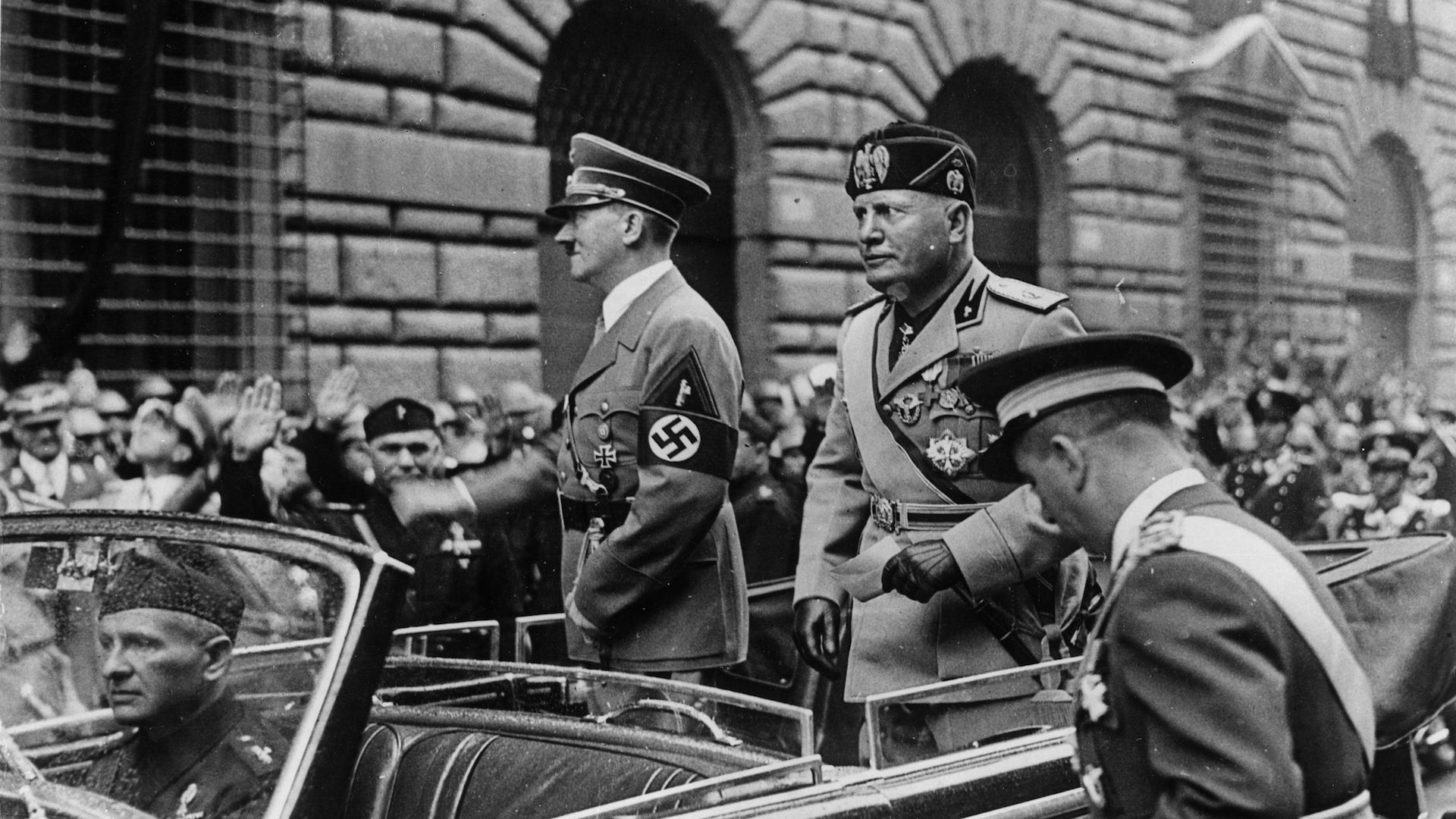 May 9, 1938: Fascism leaders, German dictator Adolf Hitler and Italian dictator Benito Mussolini standing in the back of a car, on display as they drive through Rome.