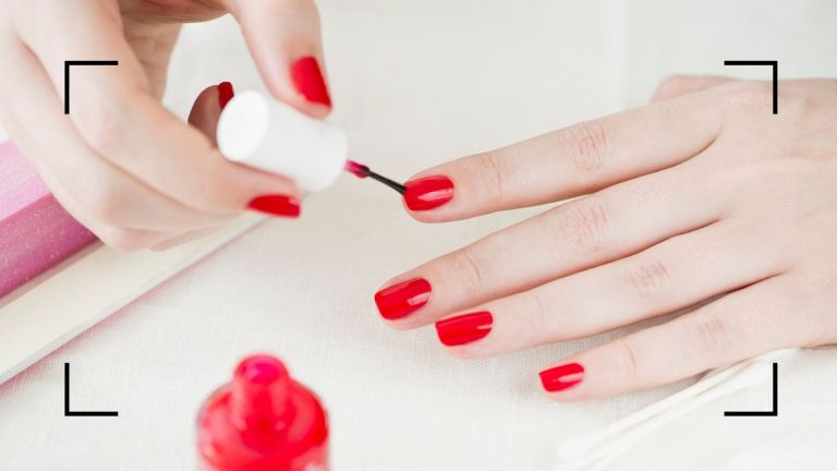 how to paint your nails main image of woman doing her own red manicure