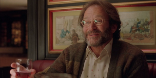 Sean Maguire (Robin Williams) sits at a restaurant holding a drink in a scene from 'Good Will Huntin