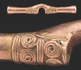 A cast nose ornament, once gold on the surface but purposely polished to be pink.