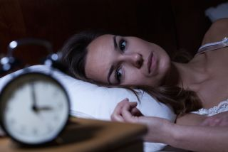 A woman lays awake in bed, looking at a clock.