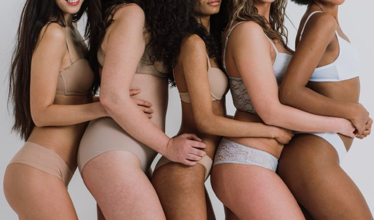 Midsection Of Multi-Ethnic Women In Bras Against Gray Background - stock photo