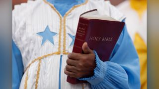A congregant holds the King James Bible during a church service in South London in 2013.