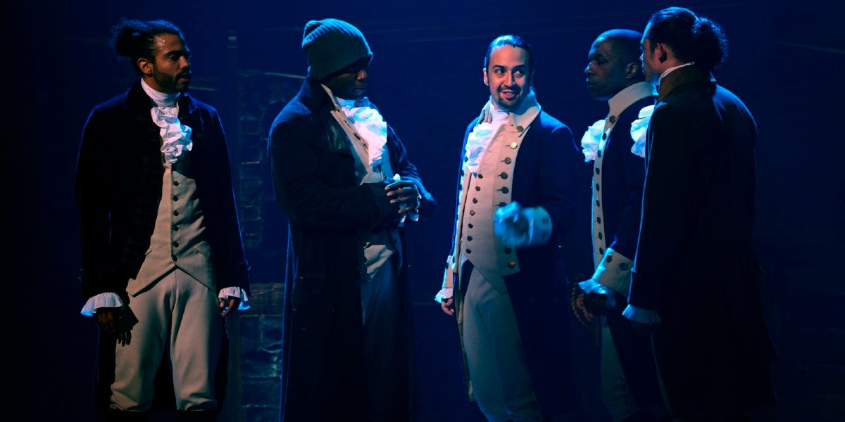 Hamilton cast standing on stage in dim light