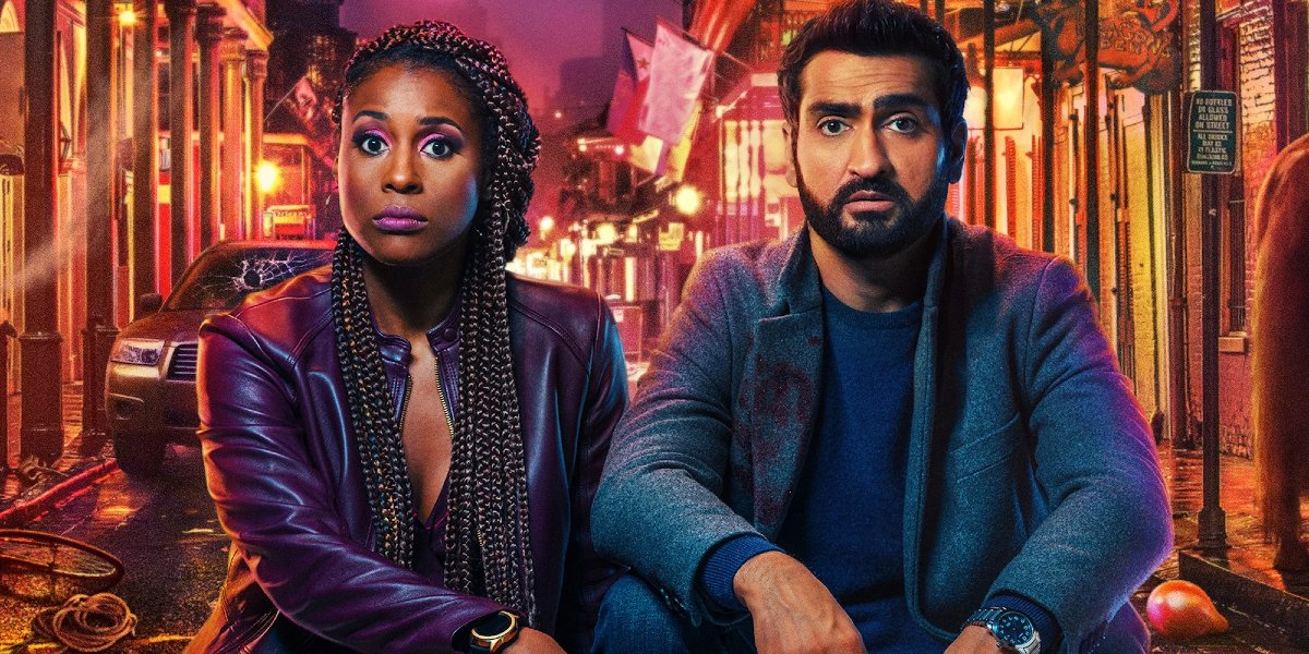 The Lovebirds Issa Rae and Kumail Nanjiani sitting in front of a chaotic street, straight faced