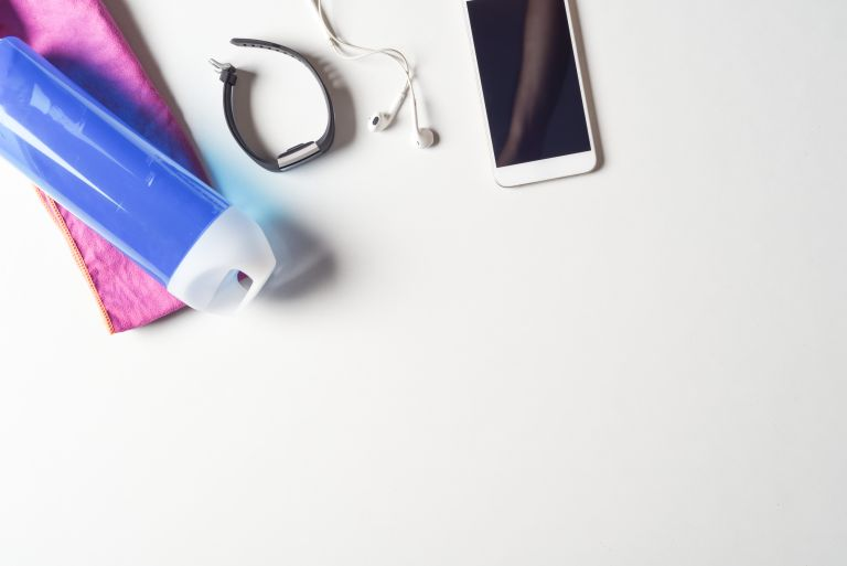 phone, headphones, fitness tracker and water bottle on a white background