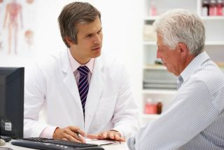 An older man talks with a doctor.