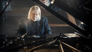 A photograph of Rick Wakeman sat at the piano, playing to himself