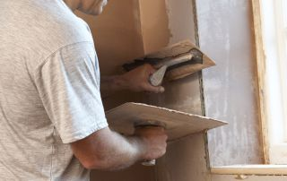 a tradeperson plastering a room
