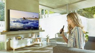 Woman holding remote in front of TV