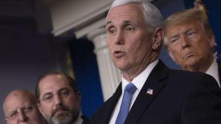 U.S. President Donald Trump listens as Vice President Mike Pence speaks during a news conference on the COVID-19 outbreak on Feb. 26, 2020.