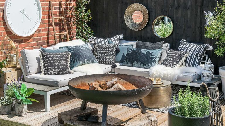 outdoor living space ideas with large fire pit and sofa on deck