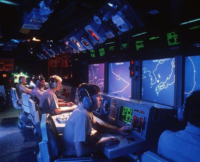 Crew members monitor radar screens in the combat information center aboard the guided missile cruiser USS Vincennes in 1988.