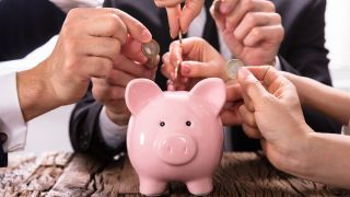 People in business suits adding cash to a piggy bank