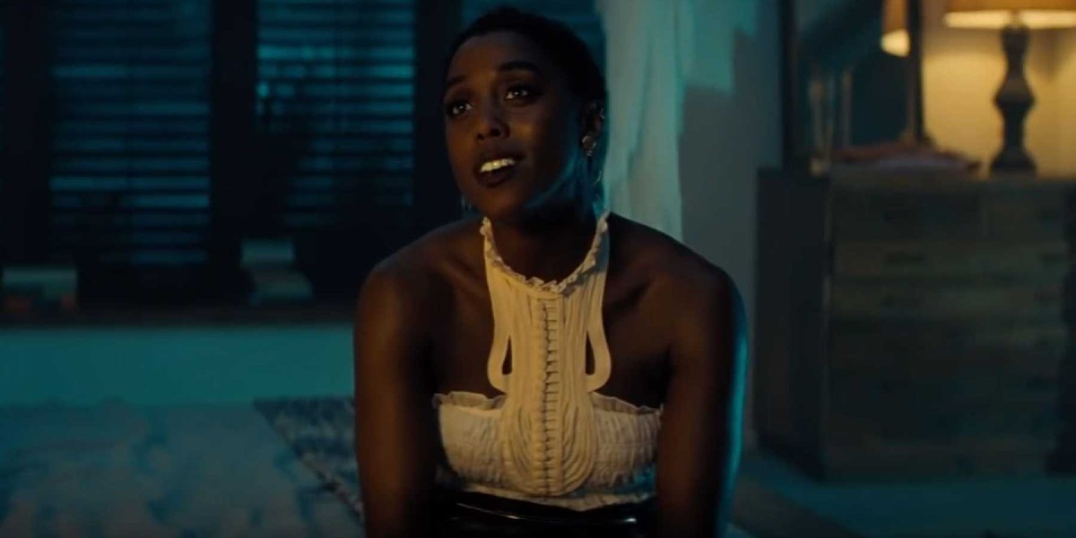 No Time To Die Lashana Lynch sitting on the side of a bed, talking